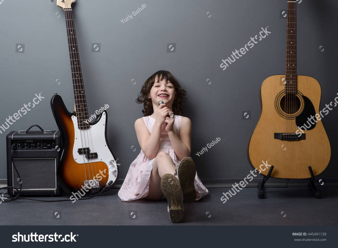 stock-photo-laughing-girl-on-the-floor-in-the-company-of-musical-instruments-harmonica-acoustic-and-bass-445491139.jpg