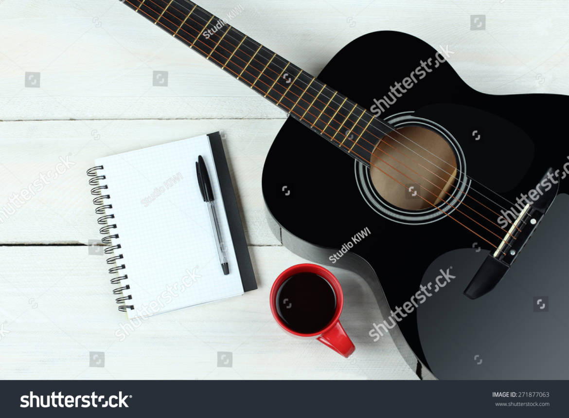 stock-photo-acoustic-guitars-with-a-notebook-and-a-cup-of-coffee-on-wood-background-271877063.jpg