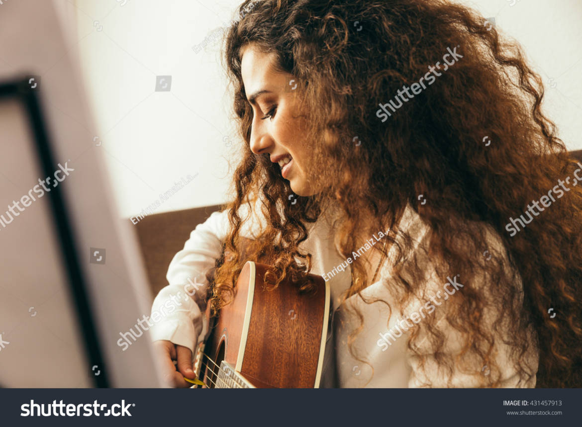 stock-photo-girl-playing-guitar-and-singing-young-woman-with-long-hair-studying-music-at-home-she-plays-431457913.jpg