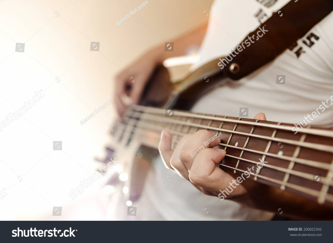 stock-photo-playing-on-electric-bass-guitar-200822342.jpg