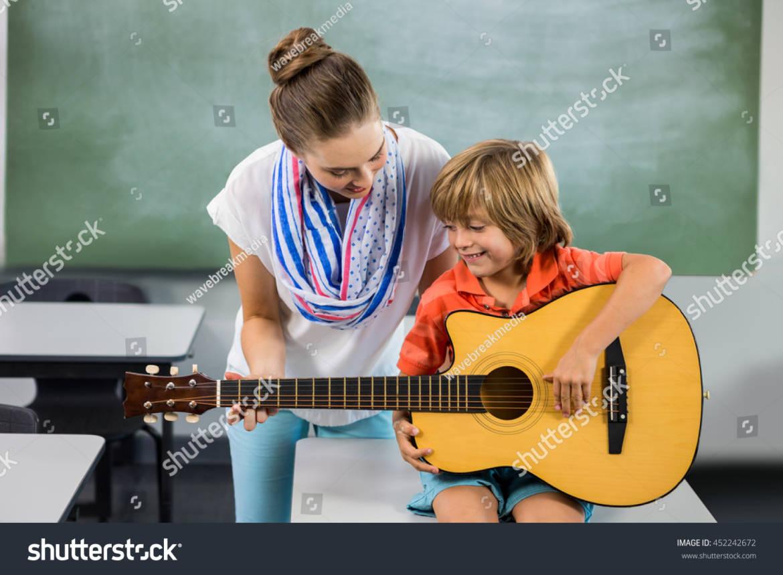 stock-photo-teacher-assisting-boy-to-play-guitar-in-classroom-452242672.jpg