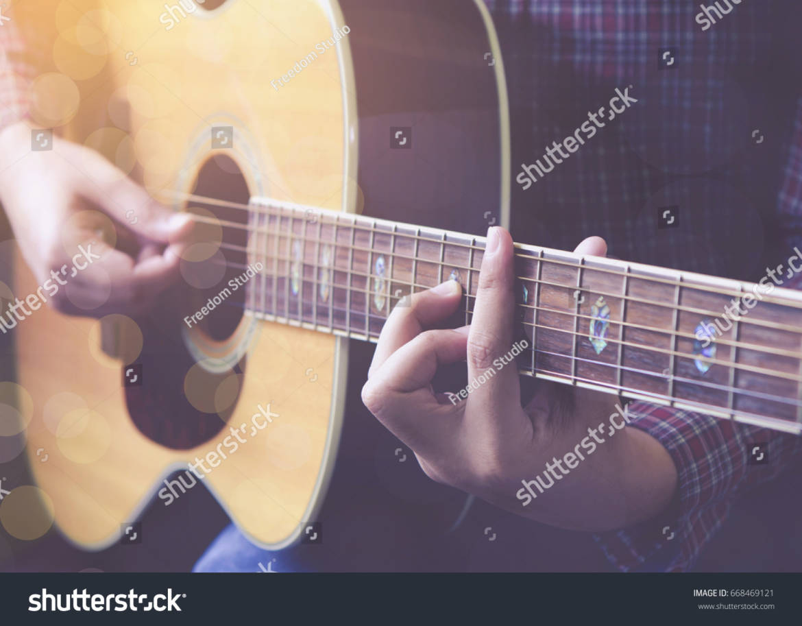 stock-photo-young-man-plays-acoustic-guitar-668469121.jpg
