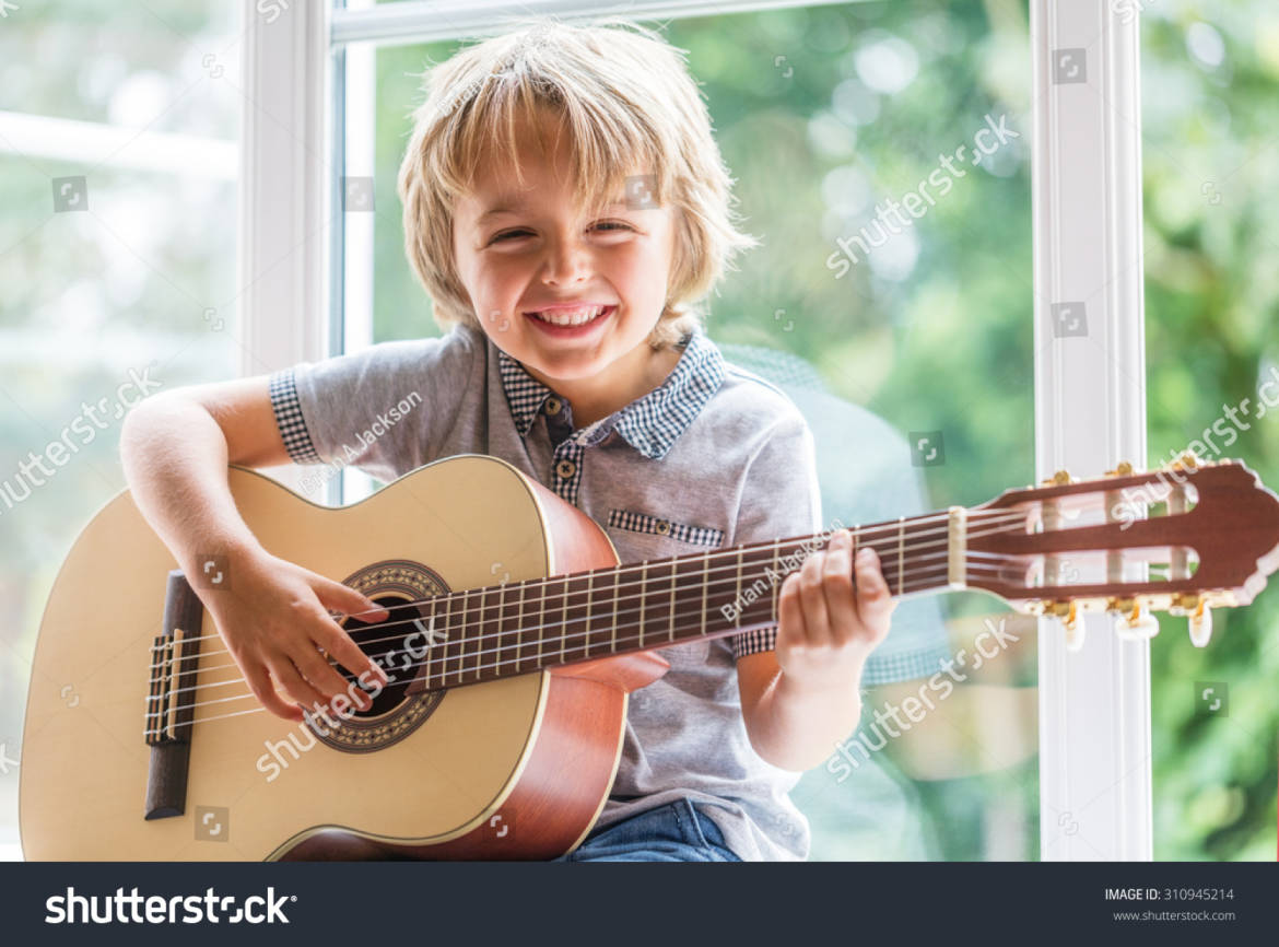 stock-photo-happy-smiling-boy-learning-to-play-the-acoustic-guitar-310945214.jpg