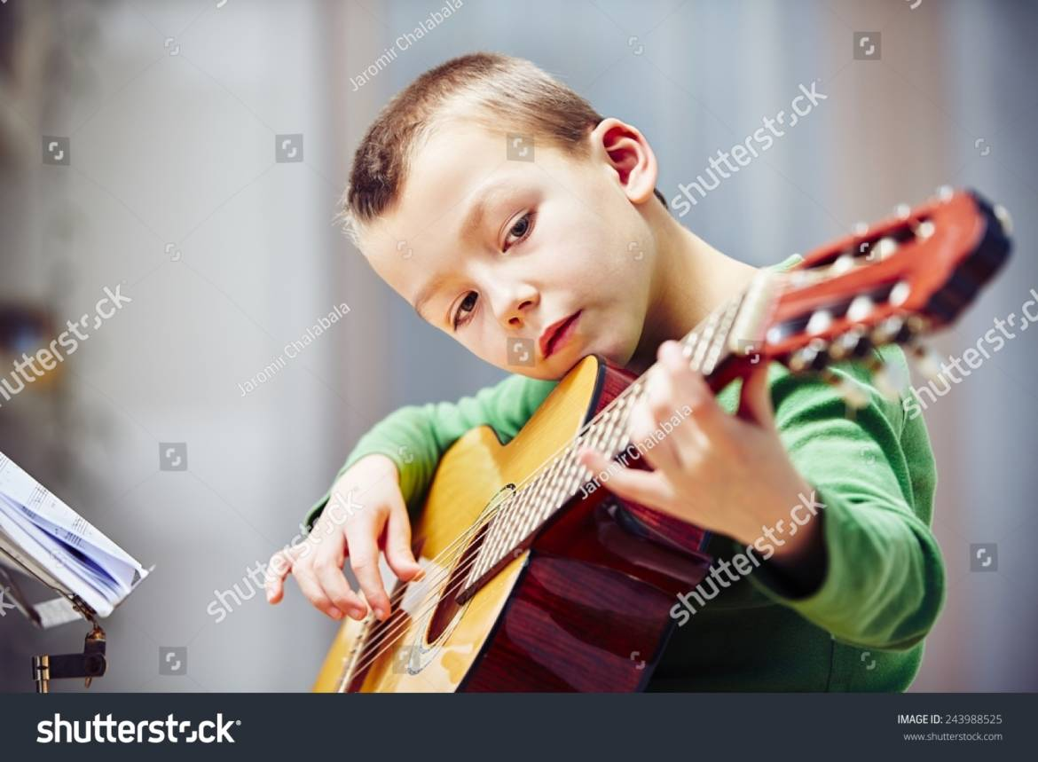 stock-photo-little-boy-is-playing-the-guitar-at-home-243988525.jpg